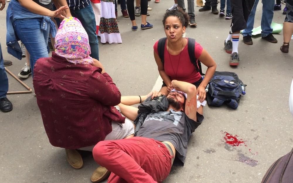 Mateus é socorrido por amigos durante o protesto (Foto: Vitor Santana/G1)